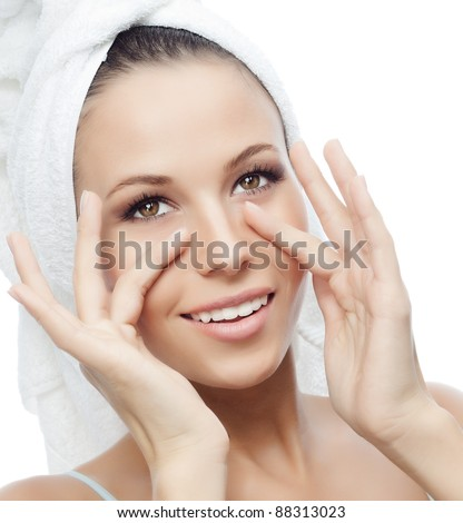 portrait of attractive  caucasian smiling woman isolated on white studio shot with towel on head making face massage - stock photo
