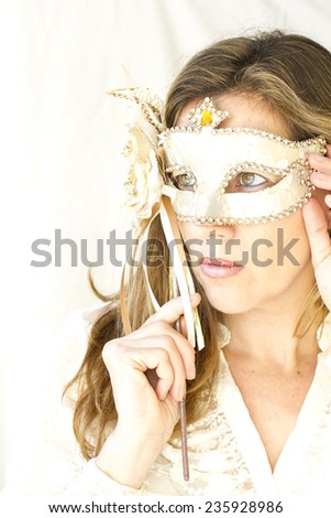 portrait of attractive caucasian woman holding a beautiful Venetian mask, photography in high key, very soft and elegant pose tones. - stock photo