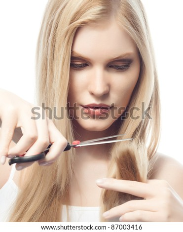 portrait of attractive  caucasian woman  with long blond hair isolated on white studio shot cutting her hair - stock photo