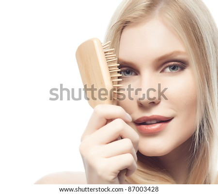 portrait of attractive  caucasian woman  with long blond hair isolated on white studio shot looking at camera with comb - stock photo