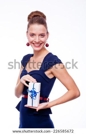 Portrait of attractive cheerful girl holding gift box with blue bow - stock photo