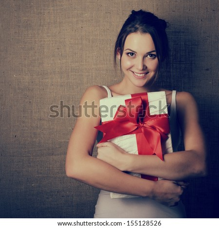 Portrait of attractive cheerful girl in sleeveless sports white shirt holding gift box with red bow over canvas background, toned and noise added - stock photo