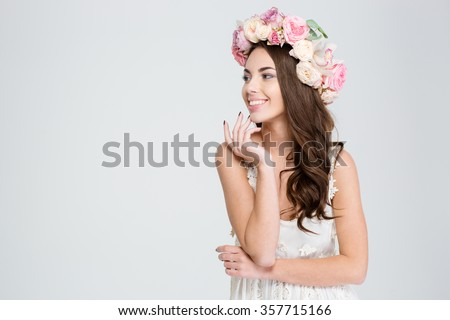 Portrait of attractive cheerful young woman in white dress and flower wreath looking away over white background - stock photo