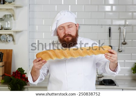 Portrait of attractive chef-cook smelling beautiful loaf of Italian Bread, young baker with beard holds a freshly loaf  - stock photo