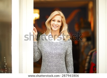 Portrait of attractive clothing shop owner standing in doorway. Smiling woman looking at camera.