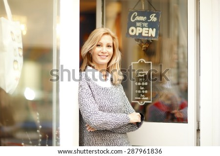 Portrait of attractive clothing store owner standing in her shop entrance. Small shop owner looking at camera and smiling.  - stock photo
