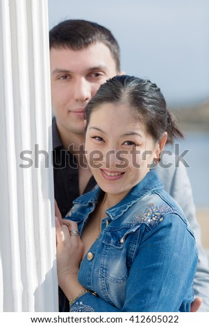 Portrait of attractive couple on open air. Asian girl and european guy posing near of column outdoors - stock photo