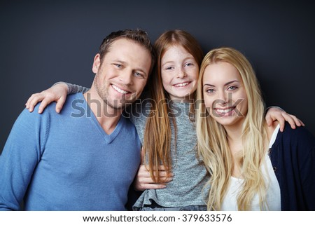 Portrait of attractive father, daughter and mother embracing together in front of dark background - stock photo