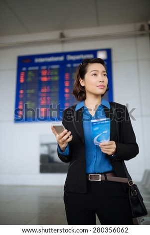 Portrait of attractive female business traveller at the airport - stock photo