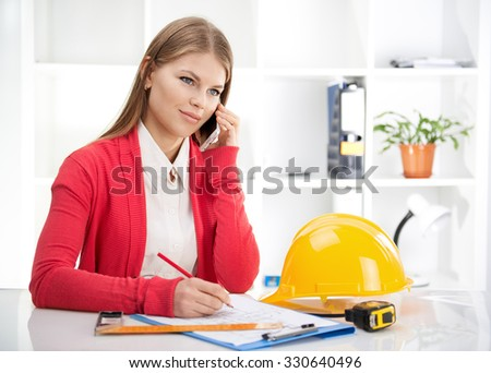 Portrait of attractive female designer drawing blueprint and talking on mobile phone. Young female engineer working on new construction project in the office.  - stock photo