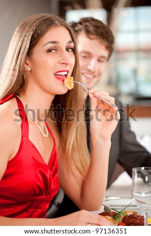 Portrait of attractive female eating food with her boyfriend in restaurant - stock photo