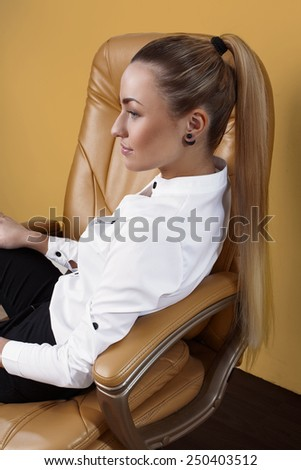 Portrait of attractive formal dressed young adult woman relaxing on armchair in office environment - stock photo