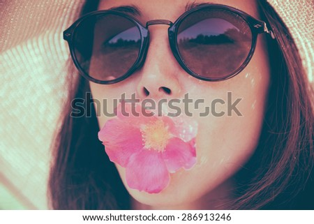 Portrait of attractive girl in sunglasses with pink flower, concept of summer mood. Fashionable and beautiful summer girl. Image with instagram color effect