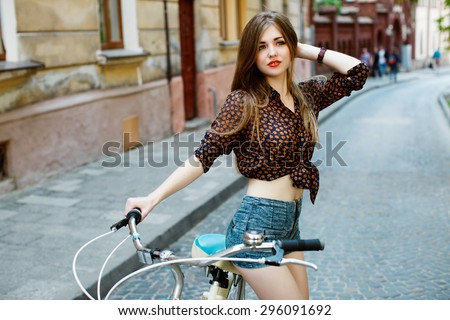 Portrait of attractive girl with perfect slim body holding bicycle handlebar wearing denim shorts and shirt. Looking somewhere. On the street. - stock photo