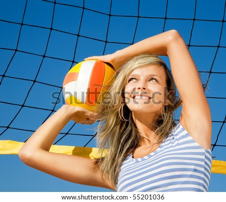 Portrait of attractive happy girl with ball near volleyball net - stock photo