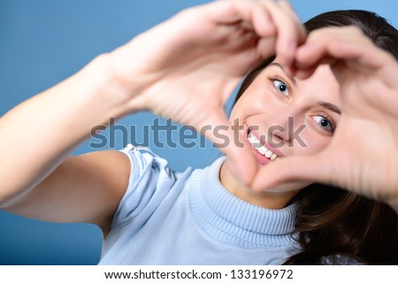 portrait of attractive happy smiling teen making heart of her hands, love holiday valentine symbol over blue