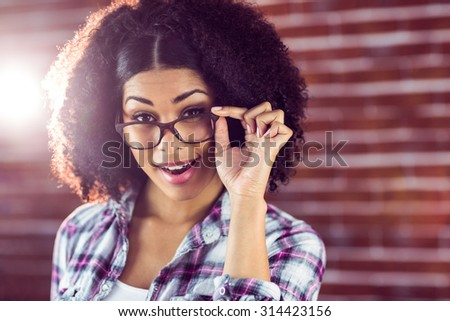 Portrait of attractive hipster posing with glasses against red brick background - stock photo