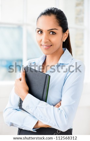 Portrait of attractive Indian businesswoman working from home - stock photo
