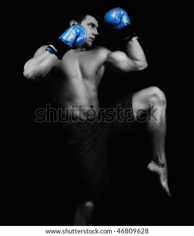 Portrait of attractive kickboxer in the dark - stock photo