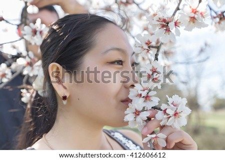 Portrait of attractive Korean girl in blossoming park. Asian girl sniffs flower of blossoming almond - stock photo