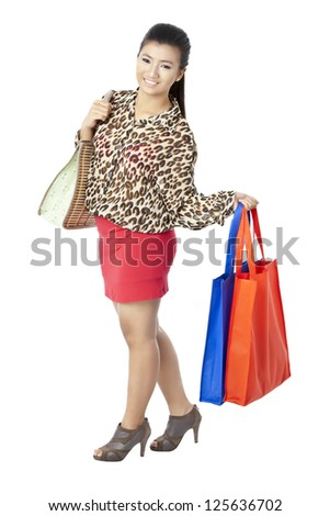 Portrait of attractive  lady smiling while holding her shopping bags against white background