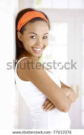 Portrait of attractive laughing ethnic woman standing at wall with arms crossed, smiling at camera.? - stock photo