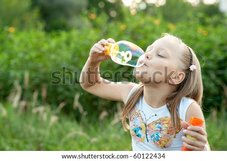 Portrait of attractive little girl with soap bubbles - stock photo