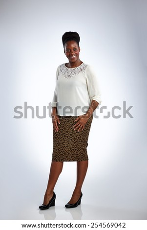 Portrait of attractive mature african woman posing in beautiful dress over white background  - stock photo