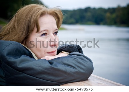 Portrait of attractive mature woman dreaming about something pleasant - stock photo
