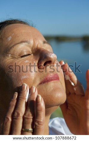 Portrait of attractive mature woman with suncream on her face to protect herself from skin cancer, isolated with blurred background and copy space.