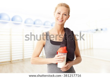 Portrait of attractive middle age woman holding in her hand a protein shaker bottle while standing at gym after fitness workout.  - stock photo