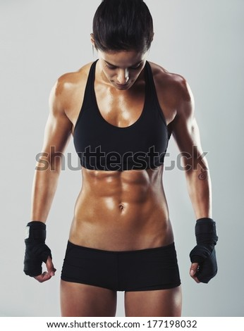 Portrait of attractive mixed race woman with muscular body looking down while standing on grey background. Fit and sexy young female bodybuilder posing. - stock photo