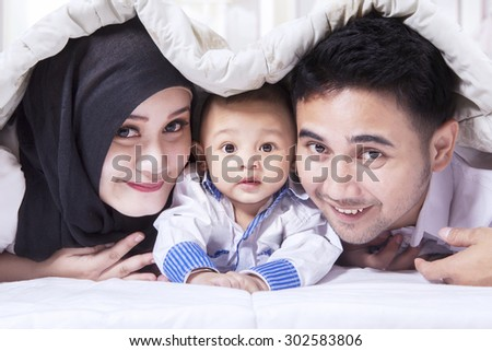 Portrait of attractive muslim family smiling on the camera with a sweet baby, shot below a blanket - stock photo