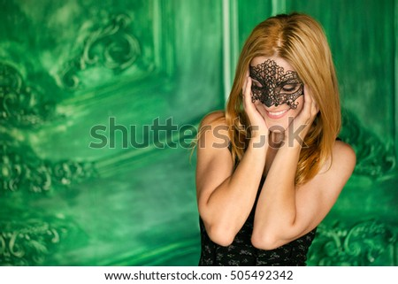 Portrait of attractive mysterious sexy young sensual woman with blond hair in lace black mask looking forward with bare shoulders in studio on wooden background, square picture