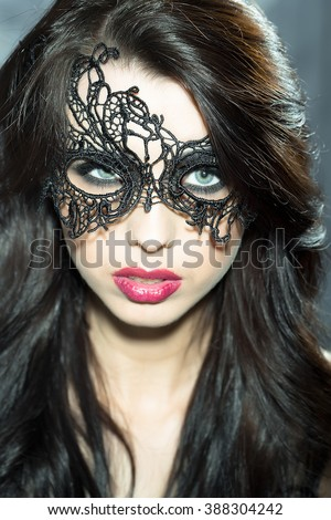 Portrait of attractive mysterious sexy young sensual woman with lush brunette hair in lace black mask looking forward with red lips, vertical picture