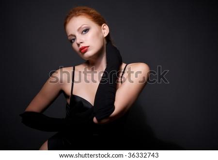 Portrait of attractive redhead model on dark background - stock photo