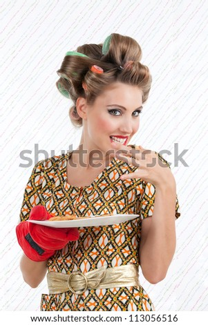 Portrait of attractive retro woman eating cookings and looking at camera. - stock photo