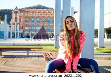 Portrait of attractive school girl posing for camera while giving a kiss, charming caucasian student sitting on the wooden campus bench against university building, cheerful teenager - stock photo