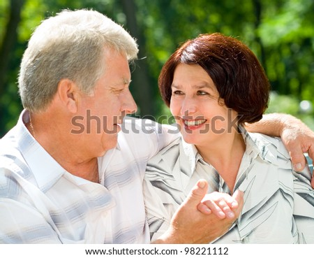 Portrait of attractive senior happy smiling cheerful couple embracing, outdoors - stock photo