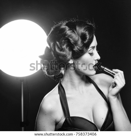 Portrait of attractive sensual glamour retro elegant young adult thoughtful woman with classic hairstyle and red lips holding lipstick in dress on black background with lamp, square picture