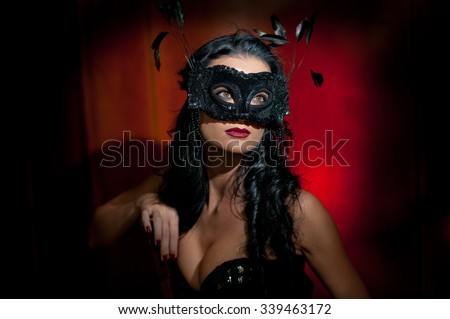 Portrait of attractive sensual young woman with mask, indoors. Sensual brunette lady posing provocatively on red background in studio. Beautiful long hair sexy woman with red lips, boudoir shot - stock photo