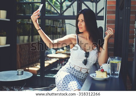 Portrait of attractive sexy lady making self portrait with her smart phone digital camera,young female with big breasts and perfect figure posing while photographing herself for social network picture