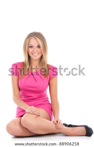 portrait of attractive smile sexy girl in pink dress sitting on the floor looking up at camera, isolated over white background - stock photo