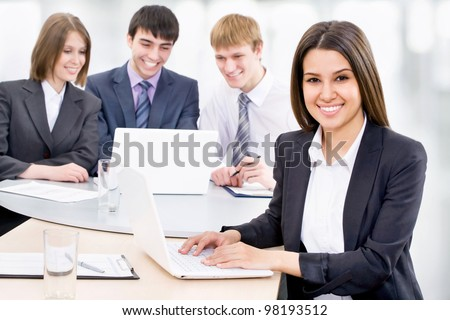 Portrait of attractive smiling business woman, team in background
