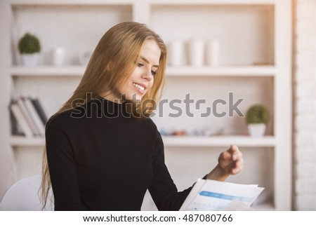 Portrait of attractive smiling businesslady dealing with paperwork in modern bright office with various items on shelves