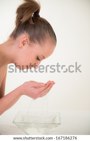portrait of attractive  smiling woman washing her face