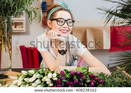 Portrait of attractive smiling young woman florist in glasses working in flower shop - stock photo