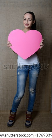 portrait of attractive smiling young woman with pink heart, love holiday valentine symbol over canvas background, toned - stock photo
