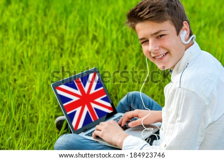 Portrait of attractive teen boy learning english on laptop outdoors. - stock photo