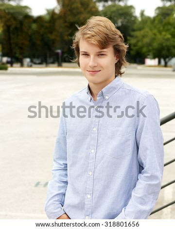 Portrait of attractive teenage boy standing against grey background - stock photo